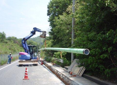 移動式クレーン仕様バックホーにて鋼製ガス管吊下ろし